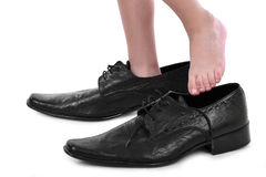 Little boy with big black shoes. Boy`s little feet in big black style shoes Stock Image