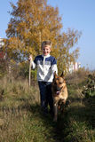 Little boy and big dog (German Shepherd ). Little boy on the walk with the big, obedient dog on suburb of the city Royalty Free Stock Images