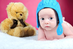 The little boy with the big eyes. On a pink background in a dark blue cap with a bear Royalty Free Stock Photography