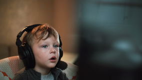Little boy in big headphones carefully watching something on a computer monitor sitting in a chair stock video footage