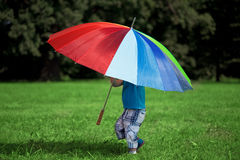 Little boy with a big rainbow umbrella Royalty Free Stock Image