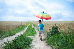 Little boy with big umbrella walking away on Stock Photography