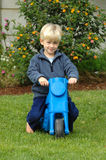 Little boy on bike. A beautiful clever little blond caucasian boy child with green eyes and happy smart smiling expression in his handsome face sitting barefoot Stock Images