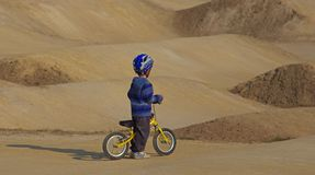 Little boy on bike. Little boy on a bicycle and wavy terrain in the background Stock Photography