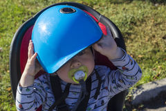 A little boy in a bike chair don't want to be at helmet Royalty Free Stock Photography