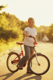 Little boy with bike on sunset Stock Photography