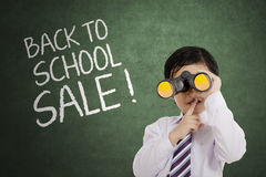 Little boy with binocular on the classroom Royalty Free Stock Photography
