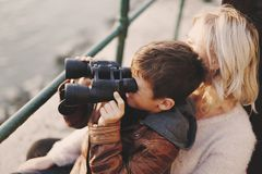 Little boy with binoculars looking at mother Stock Image