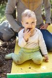 Little boy biting a cone, mother behind the boy Royalty Free Stock Image