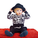 A little boy in a black hat sits Royalty Free Stock Image