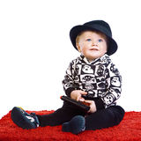 A little boy in a black hat sits Royalty Free Stock Photos