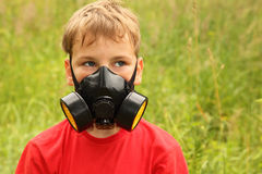 Little boy with black respirator on face Stock Images