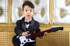 A little boy in black tuxedo stands with guitar Royalty Free Stock Photo