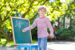 Little boy at blackboard learning to write Stock Photos