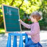 Little boy at blackboard learning to write Stock Image