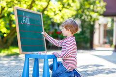 Little boy at blackboard learning to write Royalty Free Stock Photos