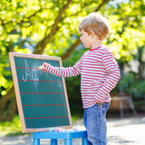 Little boy at blackboard learning to write Royalty Free Stock Image