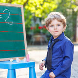 Little boy at blackboard learning to write Stock Images