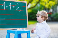 Little boy at blackboard learning to write Royalty Free Stock Photo