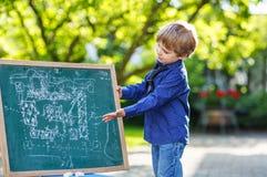 Little boy at blackboard making presentation Royalty Free Stock Photos