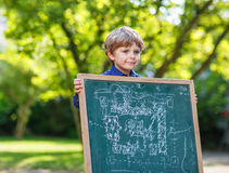 Little boy at blackboard making presentation Stock Image