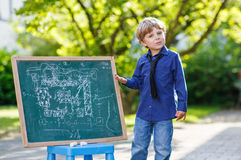 Little boy at blackboard making presentation Stock Photo