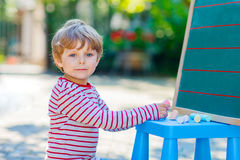 Little boy at blackboard practicing letters Stock Images