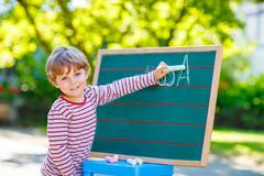 Little boy at blackboard practicing letters Stock Image