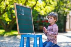 Little boy at blackboard practicing mathematics Stock Photography