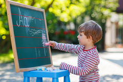 Little boy at blackboard practicing mathematics Stock Photos