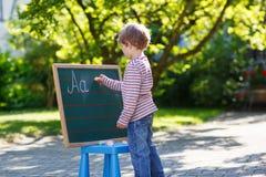 Little boy at blackboard practicing mathematics Royalty Free Stock Photos