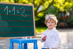Little boy at blackboard practicing mathematics Stock Photos