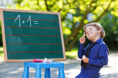 Little boy at blackboard practicing mathematics Royalty Free Stock Photo