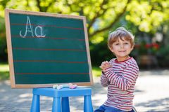 Little boy at blackboard practicing mathematics Royalty Free Stock Image