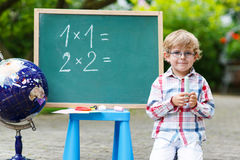 Little boy at blackboard practicing mathematics Royalty Free Stock Images
