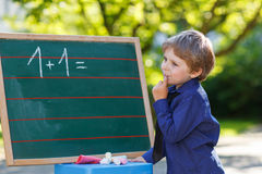 Little boy at blackboard practicing mathematics Stock Photography