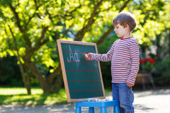 Little boy at blackboard practicing mathematics Stock Images