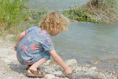Little boy with blond hair plays the waterside Royalty Free Stock Image