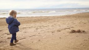 A little boy with blond hair walking along a sandy beach near the sea