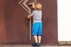 Caucasian baby boy tries to open the big door. stock image