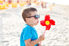 Little boy blow pinwheel. On beach Royalty Free Stock Images