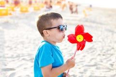 Little boy blow pinwheel Royalty Free Stock Images
