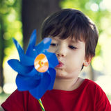 Little boy blow windmill Stock Images