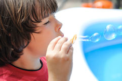 Little boy blowing bubbles Stock Photography