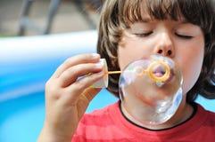 Little boy blowing bubbles Stock Photo