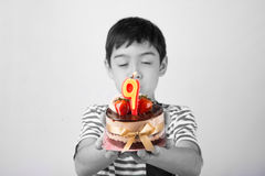 Little boy blowing candle on the cake for his birthday. With happy face 9 years old Stock Image