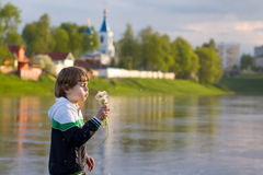 Little boy blowing dandelion on sunset on river shore. Little boy blowing dandelion with flying seeds on sunset next to a beautiful monastery on a river shore Royalty Free Stock Photo