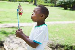 Little boy blowing pinwheel in the park Stock Photography