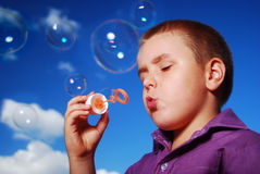Little boy blowing soap bubbles. Little 6 year old boy blowing soap bubbles outside on a sunny day with clouds and blue sky as background Royalty Free Stock Photos