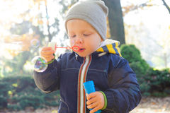 Little boy blowing soap bubbles in autumn park Royalty Free Stock Photography